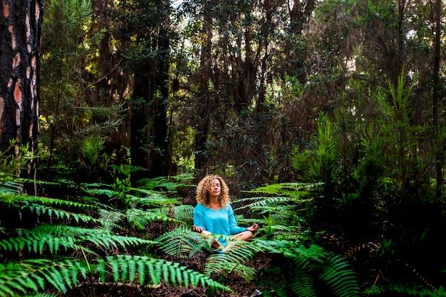 Linda senhora adulta praticando meditação consciente, sente-se no silêncio da floresta verdejante