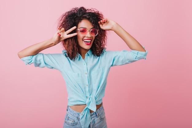 Linda senhora africana de camisa azul, expressando emoções positivas. retrato interior de uma mulher sorridente graciosa em óculos de sol rosa, posando com as mãos para cima.