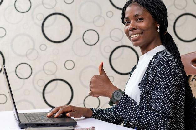 Linda senhora africana no escritório sorri enquanto levanta o polegar