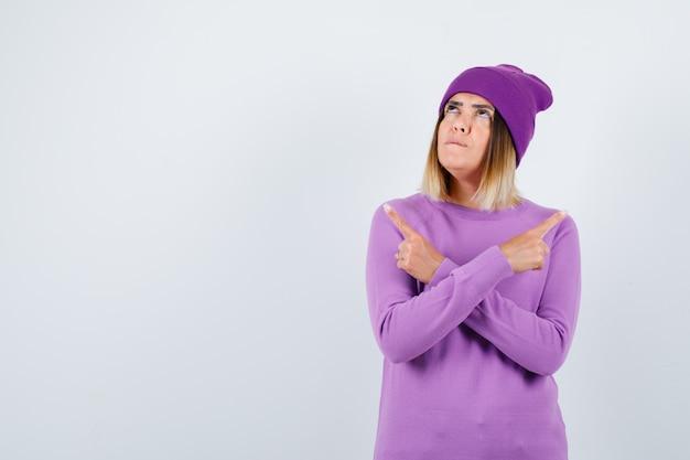 Linda senhora apontando para os lados esquerdo e direito do suéter, gorro e parecendo confiante. vista frontal.