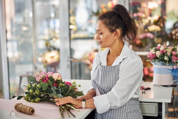 Linda senhora arrumando flores em um lindo buquê