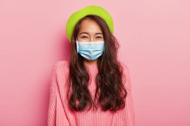 Linda senhora asiática de cabelos escuros com doença epidêmica, usa máscara médica protetora, boina verde e suéter