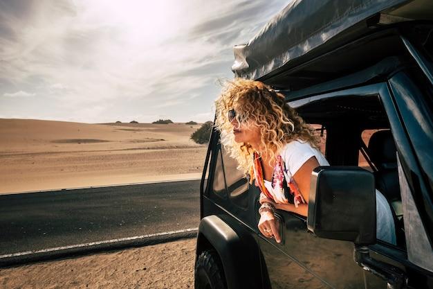 Linda senhora caucasiana feminina curtindo o vento na natureza ao ar livre em seu carro preto