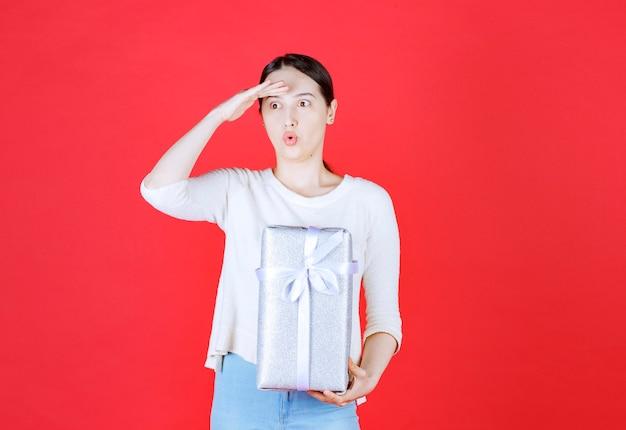 Linda senhora chocada segurando uma caixa de presente e olhando para longe