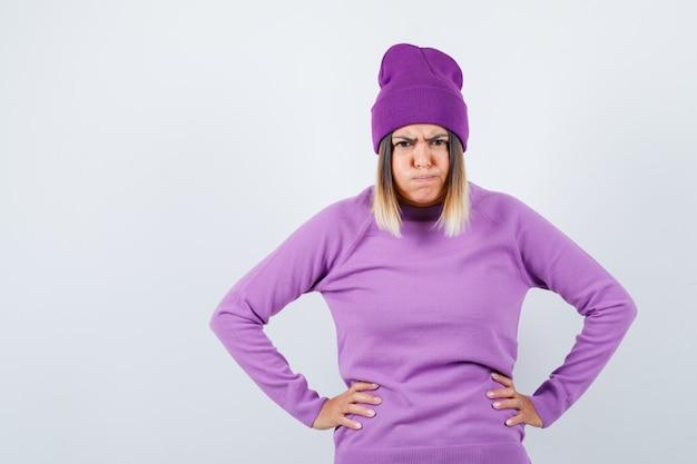 Linda senhora com as mãos na cintura, soprando as bochechas no suéter, gorro e parecendo rancoroso, vista frontal.