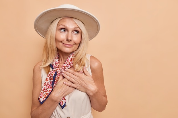 Linda senhora com cabelo loiro usa chapéu e lenço ao redor do pescoço, pressiona as mãos no coração e expressa sentimentos verdadeiros e gratidão isolados sobre o espaço bege na parede do lado direito