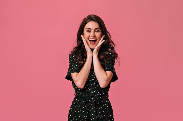 Linda senhora com roupa de bolinhas sorrindo na parede rosa