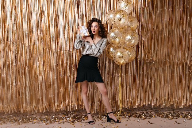 Linda senhora com roupa festiva segurando um presente no fundo de balões dourados