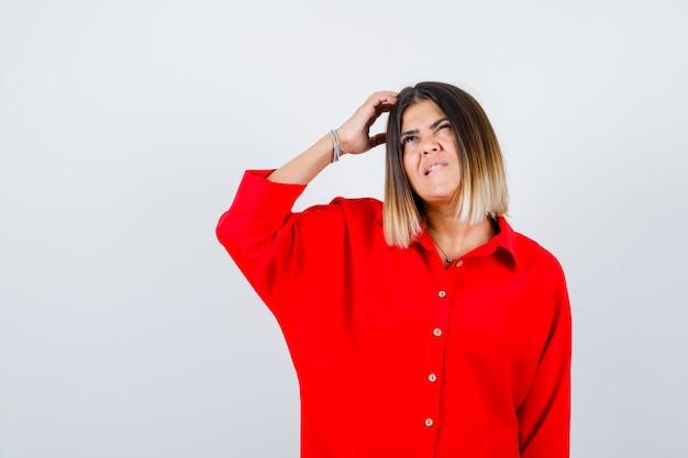 Linda senhora de blusa vermelha, coçando a cabeça, olhando para cima e parecendo esquecida, vista frontal.