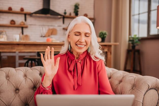 Linda senhora de cabelo comprido com blusa vermelha acenando com a mão cumprimentando amigos durante a videochamada