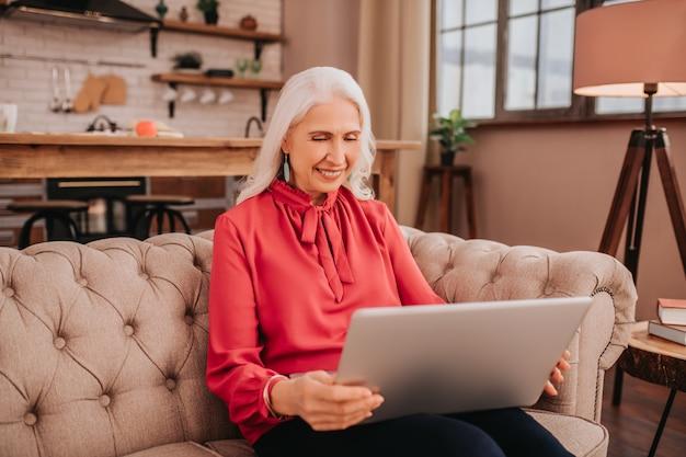 Linda senhora de cabelo comprido vestida de vermelho passando o tempo na internet