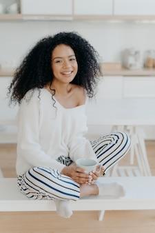 Linda senhora de cabelos cacheados bebe café ou chá de caneca branca, veste elegante suéter branco, calça listrada, posa na cozinha