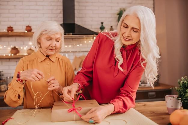 Linda senhora de cabelos compridos em vermelho abrindo uma caixa de presente