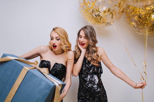 Linda senhora de cabelos compridos, posando com um monte de balões de festa e olhando para um amigo com um sorriso surpreso. aniversariante chocada usa um vestido preto segurando uma caixa de presente grande.