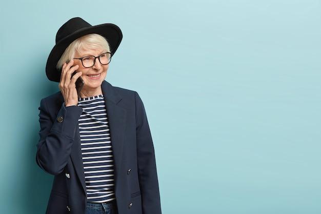 Linda senhora de cabelos grisalhos conversa ao telefone após o dia de trabalho, liga via aplicativo, discute uma nova tarefa concluída com êxito, usa um capacete elegante, isolado sobre a parede azul