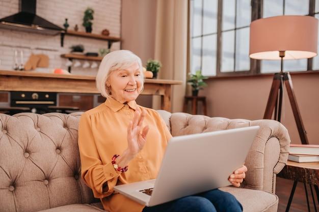 Linda senhora de cabelos grisalhos e blusa laranja em uma videochamada