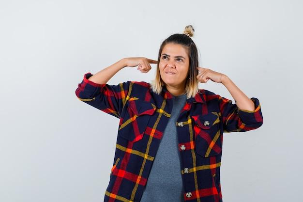 Linda senhora de camisa xadrez tapando as orelhas com os dedos, desviando o olhar, mordendo o lábio e parecendo sonhadora