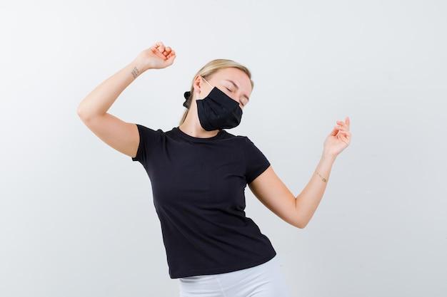 Linda senhora de camiseta preta, máscara preta mostrando gesto de vencedor isolado