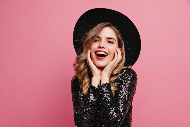 Linda senhora de chapéu preto, posando com entusiasmo. mulher branca atraente em pé na parede rosa.