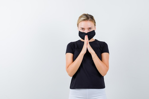 Linda senhora de mãos dadas em gesto de oração em camiseta preta, máscara preta isolada