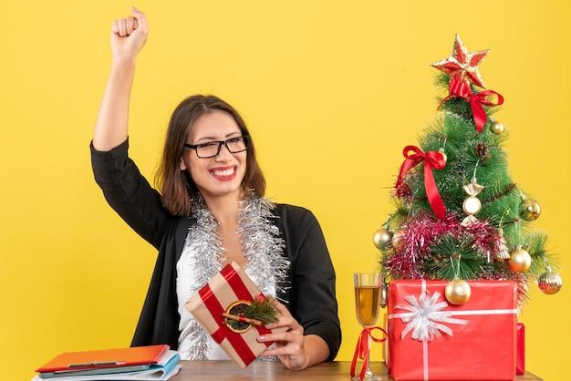 Linda senhora de negócios de terno com óculos segurando seu presente, felizmente sentada a uma mesa com uma árvore de natal no escritório
