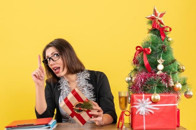 Linda senhora de negócios em um terno com óculos apontando para cima de forma surpreendente e sentada em uma mesa com uma árvore de natal no escritório em amarelo