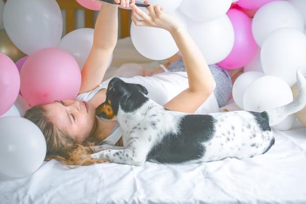 Linda senhora de pijama fazendo selfie no quarto dela usando o telefone e abraçar o cachorro dela.