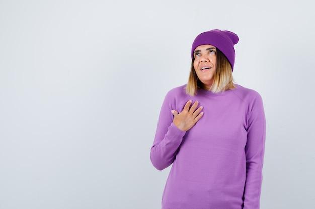 Linda senhora de suéter, gorro, mantendo a mão no peito e olhando animada, vista frontal.