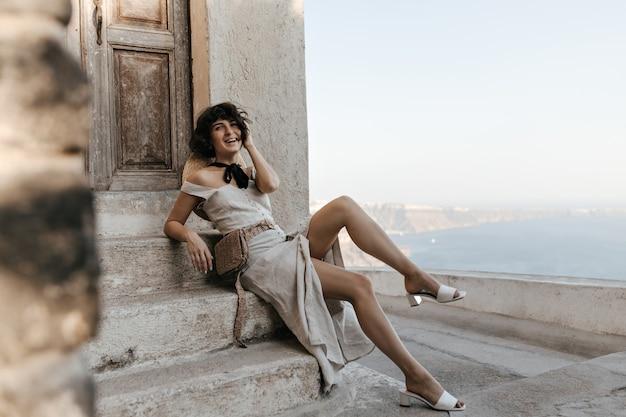Linda senhora de vestido bege midi com bolsa de palha na cintura e sorri perto da casa com vista para o mar