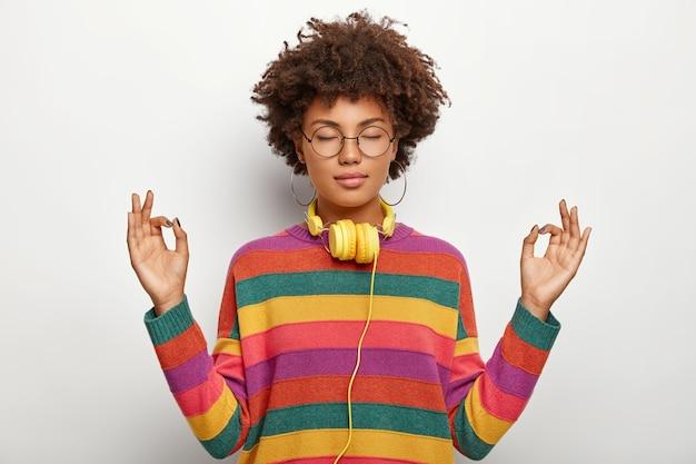 Linda senhora descontraída com penteado afro medita dentro de casa, fica de olhos fechados, sente-se satisfeita em ouvir música agradável em fones de ouvido, usa óculos, brincos, macacão listrado. linguagem corporal