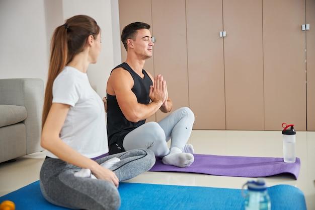 Linda senhora e o namorado fazendo ioga em casa
