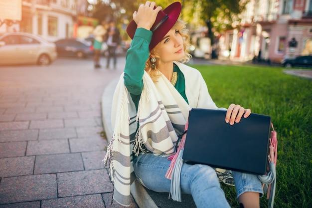 Linda senhora elegante andando na rua em capa segurando bolsa, acessórios de moda, tendência de estilo de rua de primavera, sorrindo