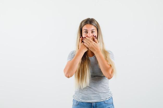 Linda senhora em t-shirt, cobrindo a boca com as mãos e olhando em silêncio, vista frontal.