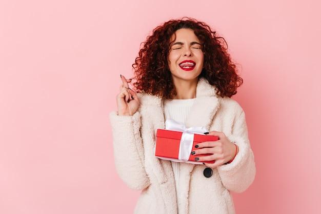 Linda senhora encaracolada fechou os olhos e cruzou os dedos. retrato de mulher de jaleco branco segurando uma caixa vermelha no espaço rosa.