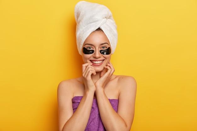 Linda senhora europeia tem tez jovem sem rugas, pele delicada, aplica colágeno escuro sob as manchas dos olhos, faz tratamento de rejuvenescimento, toma banho, envolve em toalha limpa