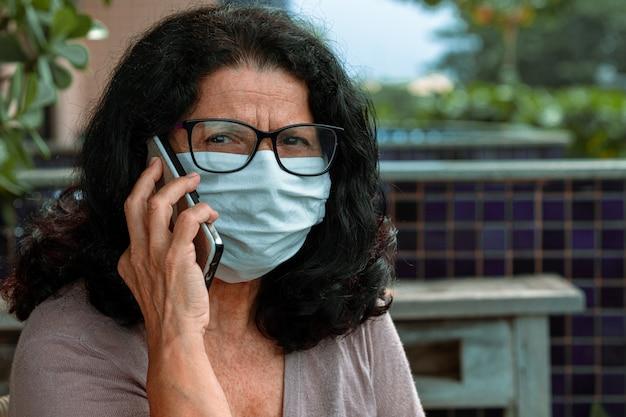 Linda senhora falando no celular, com máscara cirúrgica, protegida da pandemia