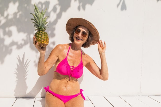 Linda senhora idosa tomando banho de sol e relaxando em uma piscina privativa durante o verão