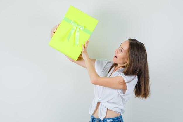Linda senhora levantando caixa de presente em blusa branca, calça jeans, vista frontal.