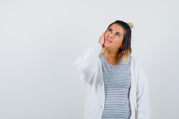 Linda senhora mantendo a mão na bochecha, olhando para cima em t-shirt, casaco de lã e parecendo esperançosa, vista frontal.