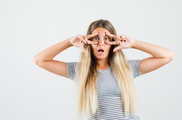 Linda senhora mostrando o sinal de v sobre os olhos na camiseta e parecendo estranha, vista frontal.