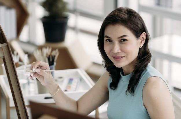 Linda senhora mulher asiática sentada e use um pincel para dor de imagem na sala. idéia para hobby, relaxamento ou trabalho artístico de casa.