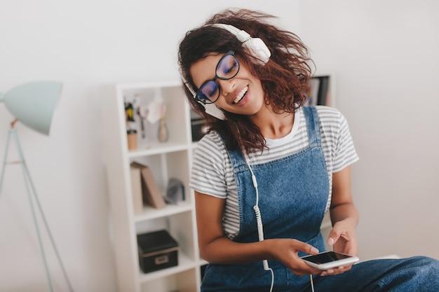 Linda senhora negra de óculos relaxando enquanto ouve música favorita com os olhos fechados no local de trabalho
