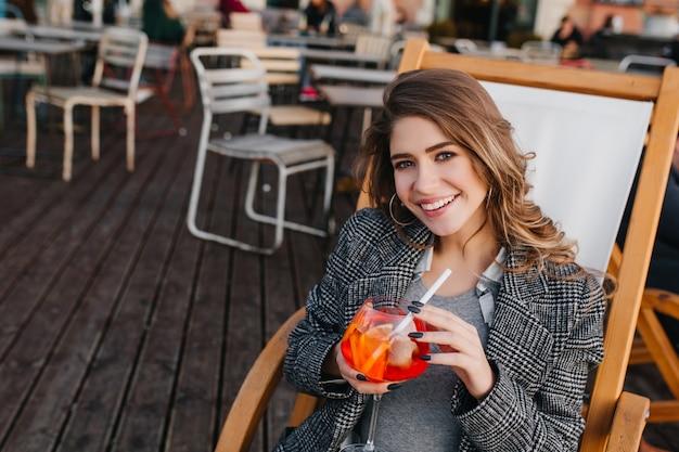 Linda senhora pálida de bom humor degustando coquetel de laranja em um café ao ar livre