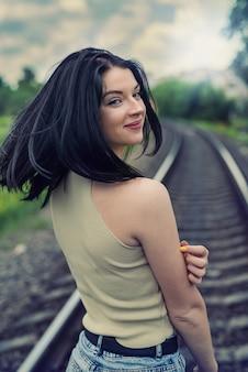 Linda senhora posando perto da ferrovia, horário de verão para a viagem