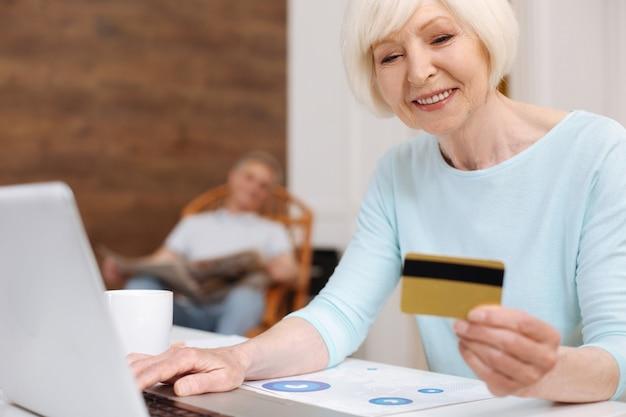 Linda senhora produtiva e entusiástica usando seu laptop para comprar coisas e pagar por elas com seu cartão de crédito