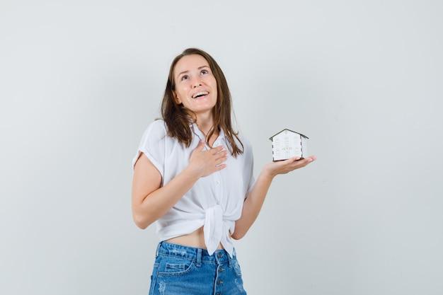 Linda senhora segurando a casa modelo, segurando a mão em seu peito na blusa branca e olhando ansiosa, vista frontal.