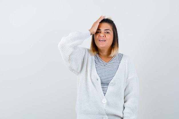 Linda senhora segurando a mão na cabeça em t-shirt, casaco de lã e aparência alegre.