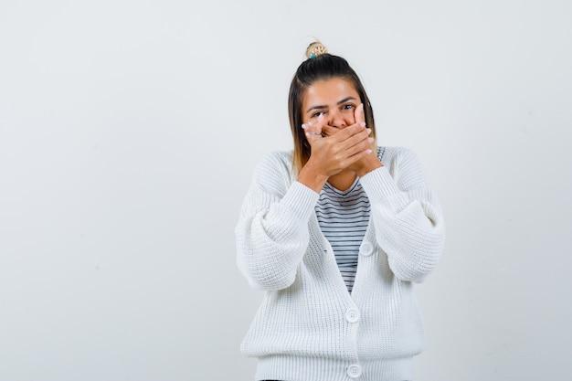 Linda senhora segurando as mãos na boca em uma camiseta, casaco de lã e olhando feliz.