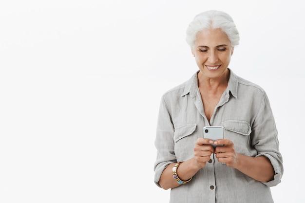 Linda senhora sênior sorridente usando telefone celular