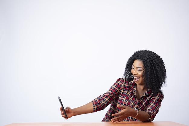 Linda senhora sentada usando seu telefone, parecendo surpresa e animada